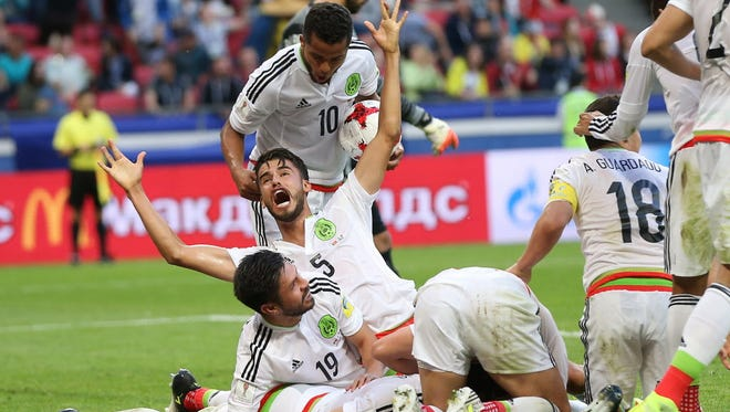 Mexico players celebrate Hector Moreno's stoppage-time game-tying goal against Portugal.