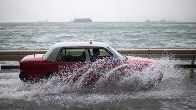 A taxi drives on a flooded street as Typhoon Hato passes by in Hong Kong on Aug. 23.