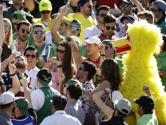 A man chugs a beer as the gallery including a Big Bird cheers him at the 16th hole during round three at TPC Scottsdale on Feb. 4, 2017 at Waste Management Phoenix Open in Scottsdale, Ariz.