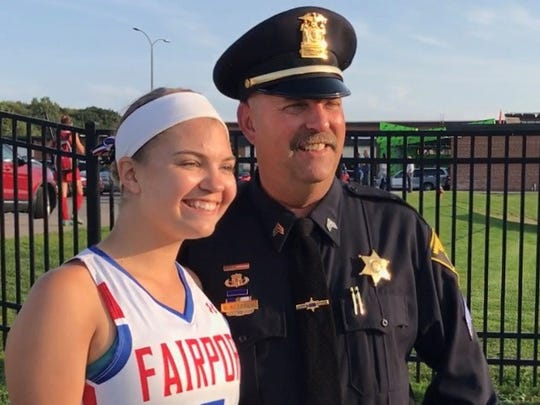 Tori Gutzmer, left, a Fairport senior, helped organize an event honoring veterans, police, fire and first responders at Monday's game on the anniversary of 9/11. Tori posed for a picture with her father, Monroe County Sheriff David Gutzmer, before the game.