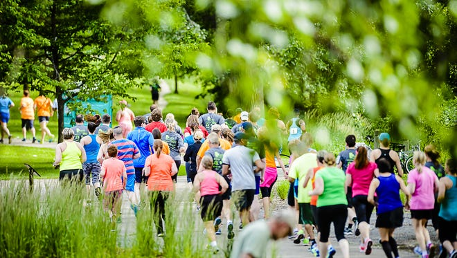 Runners round a turn during the Capitol 5K Friday June 19, 2015 at the Brenke Fish Ladder in Old Town Lansing.