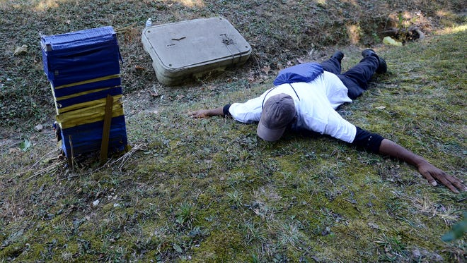L'Sana D'Jahspora lies on the grass on the side of North Parkway in Jackson, Friday afternoon, showing what he says was the area where his son was killed. D'Jahspora's son, Cinque, was shot by a Jackson police officer in 2014.