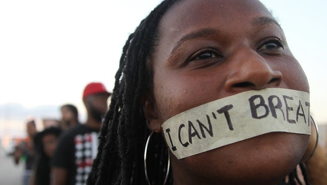 """A protestor tapes her mouth with the words """"I can't breathe.""""  Marchers shut down major midtown, Miami, on Dec. 7, 2014, in protest of police violence against civilians that caused several deaths of unarmed black boys and men."""
