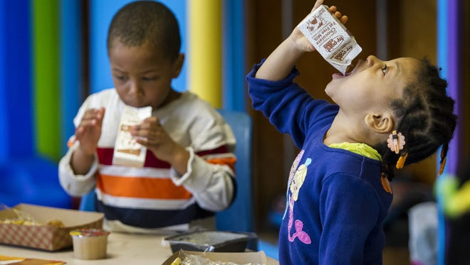 Four-year-old Ahmaree Boddy finishes off her milk as she enjoys snack time with 4-year-old Ca'lee Crippen (left) at the Kingswood Community Center in this 2015 file photo.
