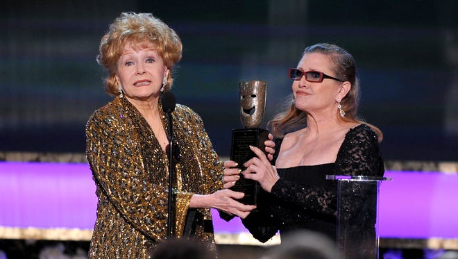 In this Jan. 25, 2015, file photo, Carrie Fisher, right, presents her mother Debbie Reynolds with the Screen Actors Guild life achievement award at the 21st annual Screen Actors Guild Awards at the Shrine Auditorium in Los Angeles.