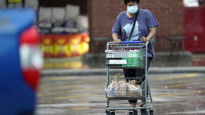 A shopper wears a mask as she pushes her grocery cart in the rain Thursday in Houston.