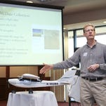 "Dr. Sean Chenoweth, associate professor of geosciences, speaks on the advantages of UAS data collection during a UAS seminar in 2014. *The drone is the Robota, LLC ""Triton."""