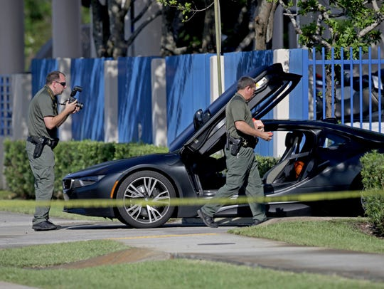 Investigators surround a vehicle after rapper XXXTentacion