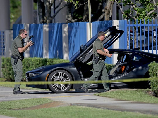 Investigators surround a vehicle after rapper XXXTentacion was shot on Monday, June 18, 2018, in Deerfield Beach. The Broward Sheriff's Office says the 20-year-old rising star was pronounced dead Monday evening at a Fort Lauderdale-area hospital.