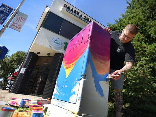 Johnny Newcomb of Bergenfield,  artist and tattooist, paints on a utility box at the corner of Main and Atlantic streets in Hackensack on June 28, 2017.