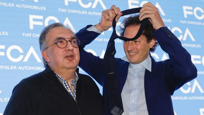 John Elkann, president of the FCA Italy group, right, gives his necktie to the famously tie-less Fiat Chrysler CEO Sergio Marchionne prior to a press conference in Balocco, Italy, Friday, June 1, 2018. In his last big presentation as CEO of Fiat Chrysler before retiring, Marchionne announced a big investment push to make more electrified cars, while acknowledging that traditional engines will continue to dominate production for some time.