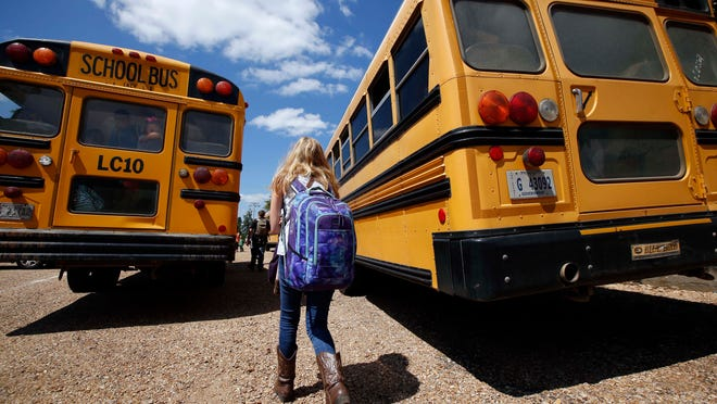 In this Aug. 13, 2014 photograph, a student prepares to leave the Enterprise Attendance Center, southeast of Brookhaven Miss. The K-12 school, like others statewide, cut back on bus purchases during the recession to save money as the state fell hundreds of millions of dollars a year short of legally mandated funding levels. If one of Enterprise's regular buses is out of service, the rural school's backup bus is 15 years old. (AP Photo/Rogelio V. Solis)