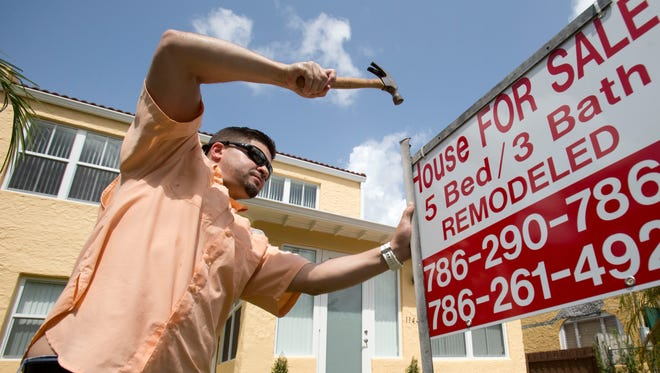 Robert Almirall, director of marketing and special assets coordinator for Mederos & Associates Real Estate, puts up a sign in front of a home in the Shenandoah neighborhood of Miami.