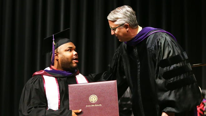 Former ASU football player Angelo Richardson receives his Master of Sports Law & Business diploma from Dean Douglas J. Sylvesterof the Sandra Day O'Connor College of Law on Wednesday, May 10, 2017 during commencement ceremony at Comerica Theatre in Phoenix, Ariz. Richardson was paralyzed from waist down after a shooting in 2006 which ended his football career. ASU honored his scholarship.