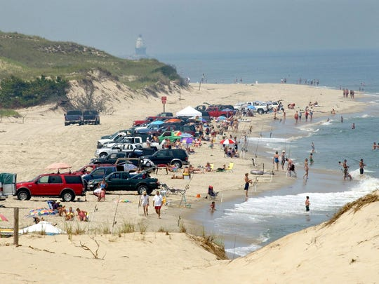 Beach-goers fish and swim at Cape Henlopen State Park. New cabins are being built at the park.