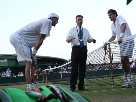 Referee Soeren Friemel calls off the epic men's singles match between John Isner, left, and Nicolas Mahut because of bad light on June 23, 2010.