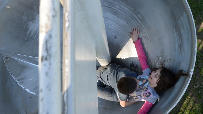Morgan Hoos, 6, left, and Grace Callahan, 7, play on a slide at Maplewood Park in Centerville.