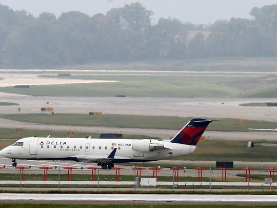 Two Delta Connection jets taxi to a runway for takeoff at Cincinnati/Northern Kentucky International Airport.