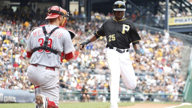 Pirates right fielder Gregory Polanco crosses home plate to score a run as Reds catcher Devin Mesoraco looks on during the fifth inning Thursday at PNC Park.