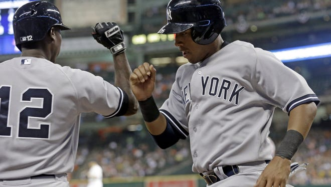 The Yankees' Yangervis Solarte, right, knocks arms with Alfonso Soriano after scoring from third base on a Carlos Beltran bases-loaded sacrifice fly against the Houston Astros Thursday night.