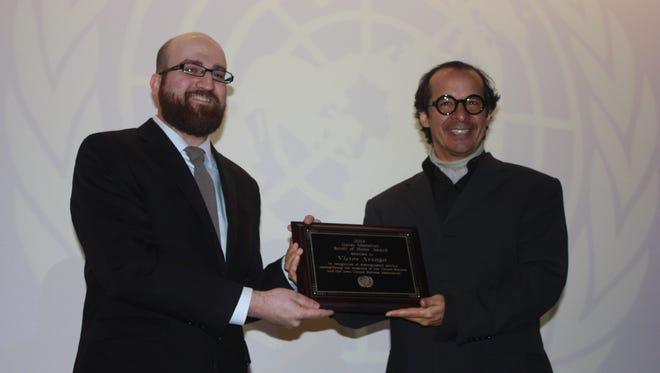 Iowa United Nations Association executive director Yashar Vasef presents the Garst Memorial Award Scroll of Honor to Victor Arango.