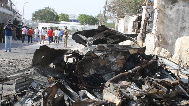 Somali soldiers stand guards by the carcass of a huge car bomb, on Feb. 21, 2014 in Mogadishu.