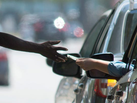 A panhandler accepts money from a motorist in this file photo from Pensacola, Florida.