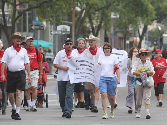 A group marches to support equal rights for farm workers during the Labor Day Parade in Rochester on  September 2, 2013.