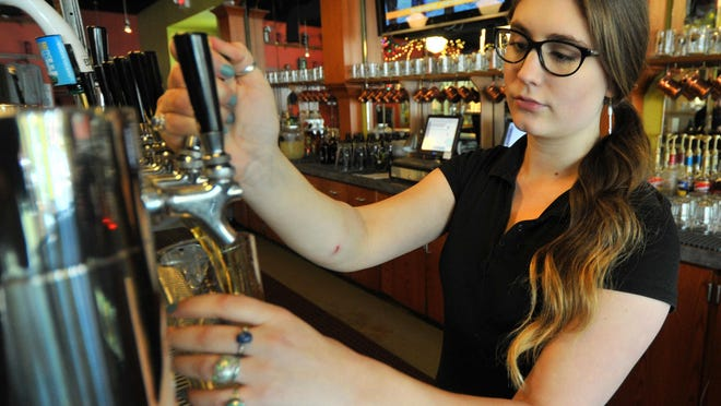 Manager Shelby Champagne pours a glass of beer at Red Eye Brewing Company in Wausau.