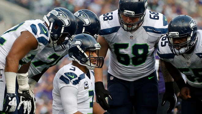 Seattle Seahawks quarterback Russell Wilson (3) huddles with teammates during an NFL football game against the Baltimore Ravens, Sunday, Dec. 13, 2015, in Baltimore.