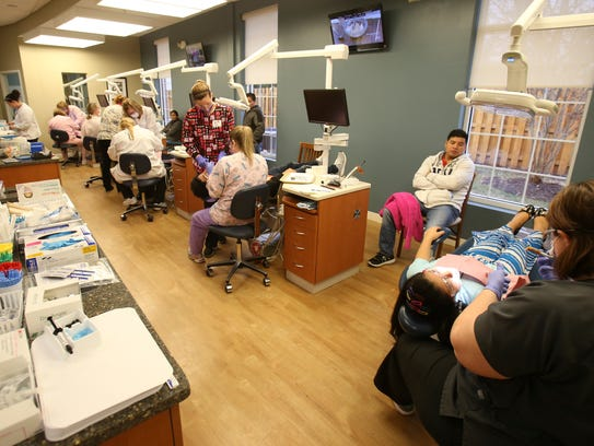 """Volunteer dental hygienists treat a stream of patients at the Delaware State Dental Society's annual """"Give Kids a Smile"""" event in Dover."""