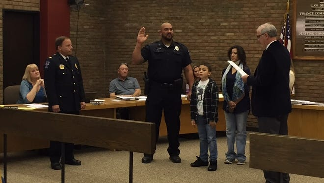 Bucyrus Police Officer John Dorsey, center, is promoted to lieutenant by Mayor Jeff Reser, right, during a ceremony Tuesday in Bucyrus City Hall as Dorsey's family, City Council members and Bucyrus Police Chief David Koepke, left, look on.