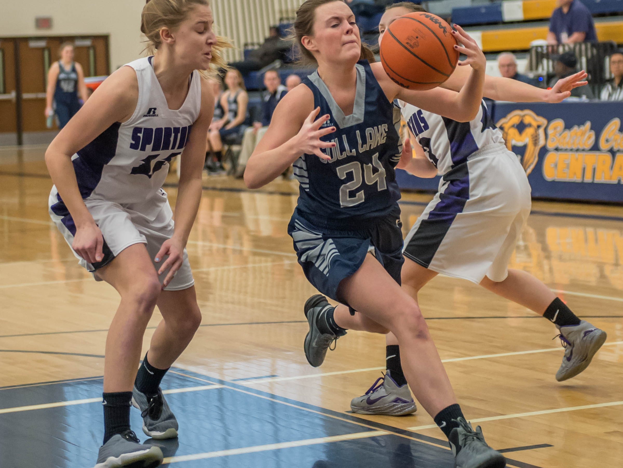 Gull Lake's Lauren Nusbaum (24) drive to the basket while being guarded by Lakeview defenders during district game Wednesday evening.