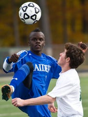 Left, U-32 #17 Dashiell Verily pops the ball over Woodstock #13 Mason Thompson but draws the whistle during the Division II boys soccer championship played at South Burlington High School Saturday, October 31, 2015.