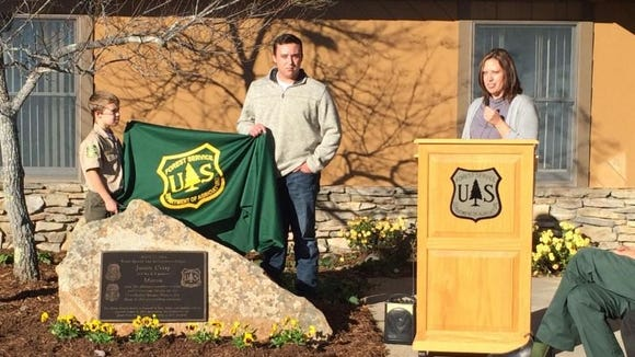 Logan, Garrett and Amanda Crisp unveil the Memorial Stone in honor of their father and husband Officer Crisp.