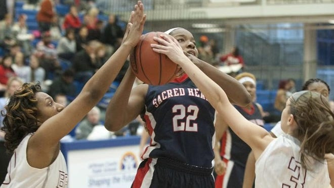 Ballard Bruins guard Aundrea Matchen, left, and guard Briana Mishler, right, try to deny Sacred Heart Academy Valkyries' guard Raven Merriweather a basket. Sacred Heart defeated Ballard 46-39 in the Kentucky 7th Regional Girls Basketball Championship.