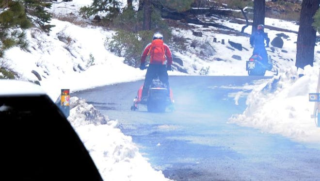 Snowmobilers on Monday head from California, between Truckee and Lake Tahoe, up to the site of a small plane crash about three miles away near the Nevada state line Monday. One person survived but another was killed in the crash