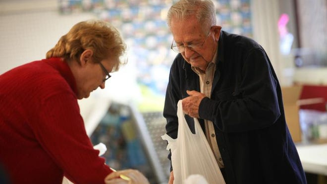 Volunteers Kathy Huston and Ron Grier help arrange food packages at First Presbyterian Church in Smyrna during their weekly food bank distribution.