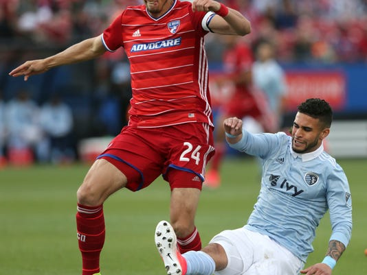 FC Dallas defender Matt Hedges (24) and Sporting Kansas City forward Dom Dwyer (14) vie for control of the ball during the first half of an MLS soccer match in Frisco, Texas, Saturday, April 22, 2017. (AP Photo/LM Otero)