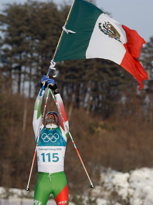German Madrazo, of Mexico, holds up his counties flag after finishing last in the men's 15km freestyle cross-country skiing competition at the 2018 Winter Olympics in Pyeongchang, South Korea, Friday, Feb. 16, 2018. (AP Photo/Kirsty Wigglesworth)