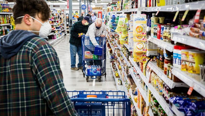 Shoppers visit Meijer while wearing masks. Under Michigan Gov. Gretchen Whitmer's executive order, shoppers must wear masks inside stores, punishable by a $500 fine.