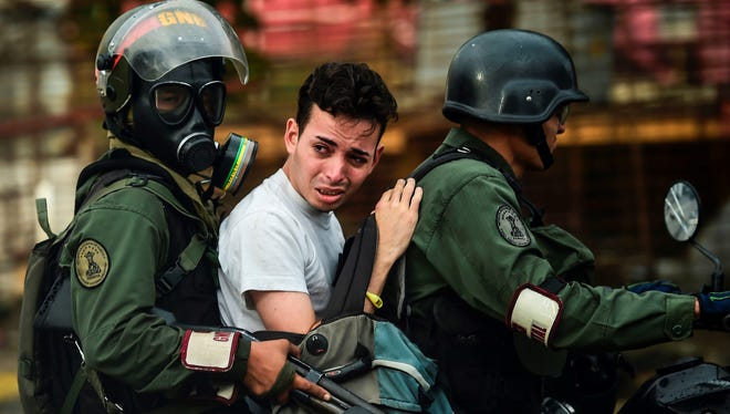An anti-government activist is arrested during clashes in Caracas on July 28, 2017. Protesters took over streets in Caracas on Friday in a show of defiance to President Nicolas Maduro, as the crisis gripping Venezuela turned deadlier ahead of a controversial weekend election that has earned international scorn.