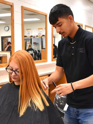 Southern Tech student Francisco Doughty practices his craft on classmate Heaven West. Training for and excelling in a field dominated by women, Doughty has been nominated for the statewide Breaking Traditions Award.