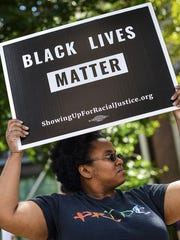 A woman holding a Black Lives Matter poster at a Louisville rally.