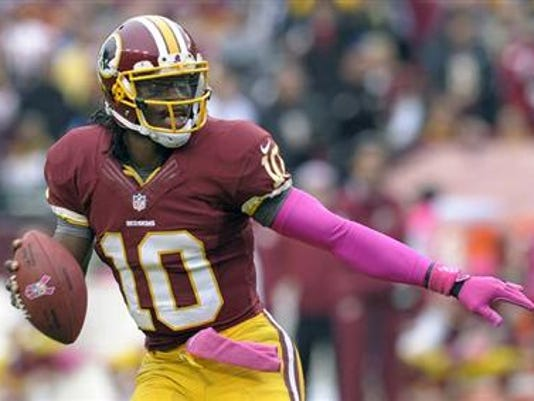 Washington quarterback Robert Griffin III looks for an open man to throw to during the second half of the Redskins' loss to the Atlanta Falcons in Landover, Md., Sunday, Oct. 7, 2012. (AP Photo/Susan Walsh)