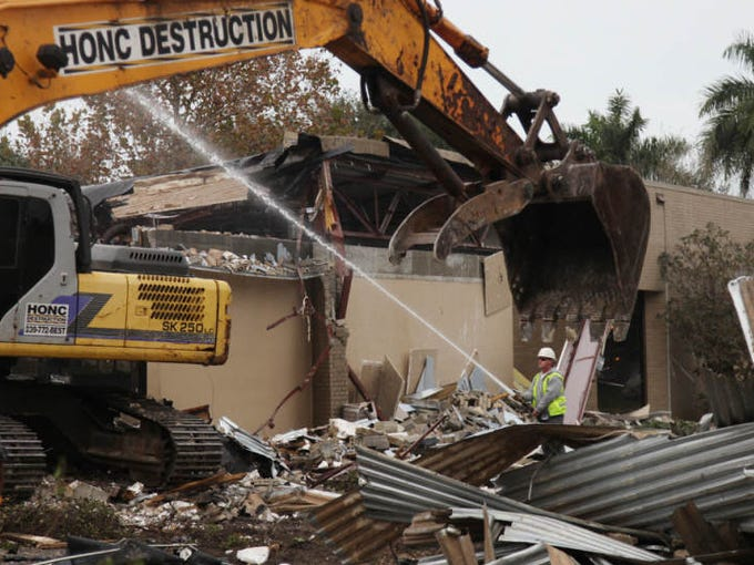 Crews with Honc Destruction in Cape Coral demolish the old Fort Myers Public Library building on Wednesday.