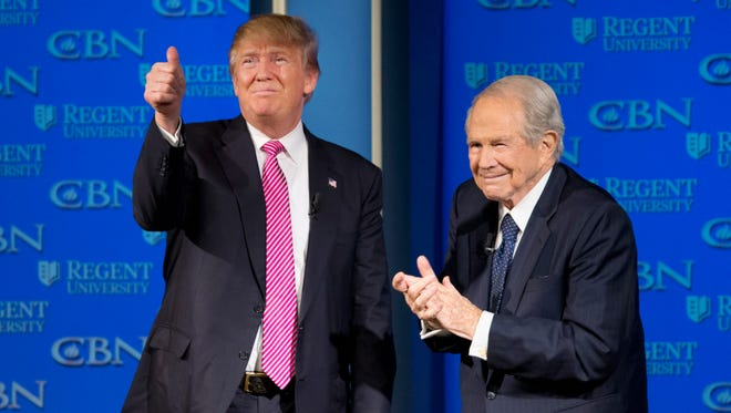 Republican presidential candidate Donald Trump, accompanied by Rev. Pat Robertson, gives a thumbs up to the crowd after speaking at Regent University in Virginia Beach, Va., Wednesday, Feb. 24, 2016.  (AP Photo/Steve Helber)