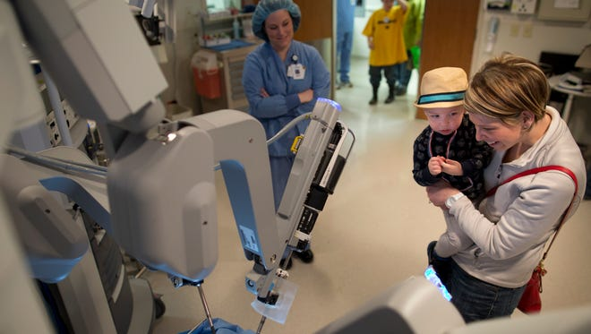 Megan Cottone, of Port Huron, looks at a surgical robot with her son Wesley, 23-months, during the Children's Fun and Fitness Festival Saturday at McLaren Port Huron.