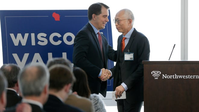 Wisconsin Gov. Scott Walker (left) shakes hands with Louis Woo, special assistant to Foxconn Chairman Terry Gou, Tuesday at a news conference at the Northwestern Mutual Tower and Commons in downtown Milwaukee. Foxconn announced its plans to buy the 132,800-square-foot building at 611 E. Wisconsin Ave. from Northwestern Mutual Life Insurance Co.
