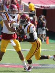 Iowa State Cyclones quarterback Sam Richardson (12) hands the ball off to running back Mike Warren (2) in the game against the Texas Tech Red Raiders at Jones AT&T Stadium.